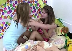 Two playful amateur chics kiss zealously in the bed